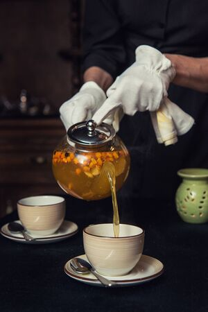 Pouring tea with sea buckthorn honey and herbs in glass teapot
