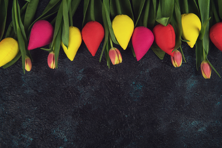 Handmade and real tulips on darken concrete background for Mothers Day, spring time or Easter theme. Banco de Imagens