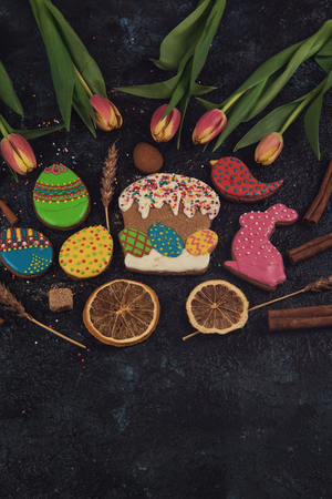 Tulips and gingerbread cookies on darken concrete background for Easter. Banco de Imagens