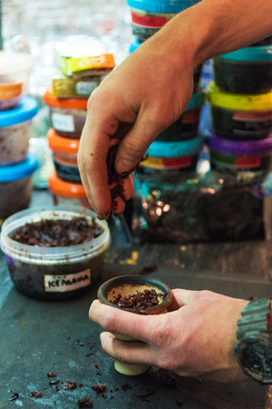 Shisha hookah preparing by barman. Bartender lays tobacco for smoking in hookah Stock Photo