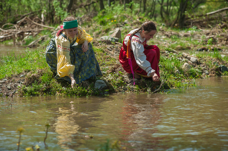 TOPOLNOE, ALTAY, RUSSIA - May 27, 2018: Folk festivities dedicated to the feast of the Holy Trinity. Ancient Russian rite: girls are sinking their birch wreaths