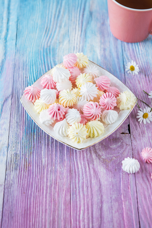 Tasty different marshmallows with chamomile flower on a color gradient background Stock Photo