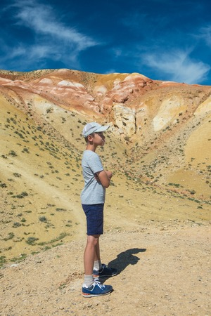 Teen boy in valley of Mars landscapes in the Altai Mountains, Kyzyl Chin, Siberia, Russia