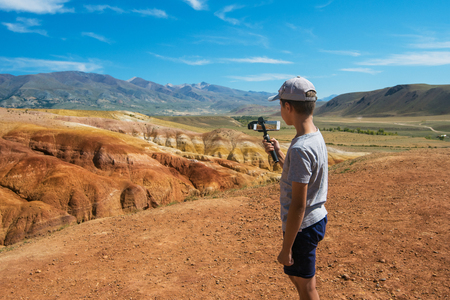 Teen boy recording video on phone in valley of Mars landscapes in the Altai Mountains, Kyzyl Chin, Siberia, Russia