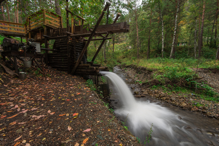 Rustic watermill with wheel being turned by force of falling water from Altai mountain river. Slow shutter speed.
