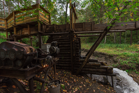 Rustic watermill with wheel being turned by force of falling water from Altai mountain river. Short shutter speed.