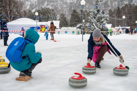 BYURIZOVAYA KATUN. ALTAISKIY KRAI. WESTERN SIBERIA. RUSSIA - DECEMBER 1, 2018: Young woman teaches children in curling game on Folk winter holiday called the Altaiskaya Zimovka holiday - the first day of winter on December 1, 2018 in Altayskiy krai, Siber
