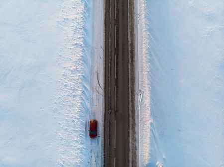 Aerial view of a road with car in winter landscape, top view