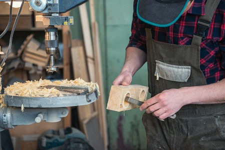 Carpenters with electric drill machine drilling wooden board at workshop. Profession, carpentry and woodwork concept. Reklamní fotografie