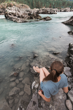 Woman resting at river in Altai Mountains territory