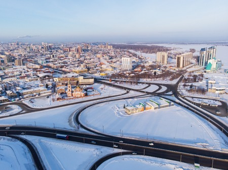 Aerial shot of road and cars driving on the road, winter sunny day in Barnaul, Siberia, Russia