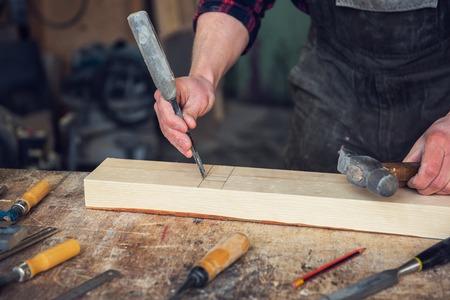 Carpintero trabajando con un cincel y un martillo en un taller de madera. Profesión, carpintería y concepto de carpintería manual.