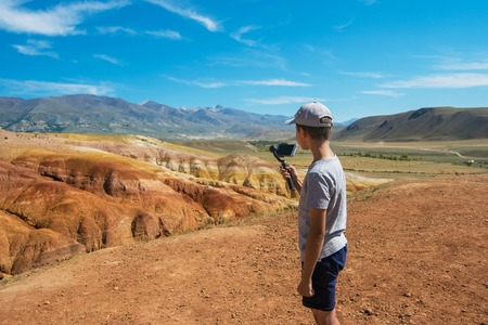Young boy in valley of Mars landscapes in the Altai Mountains, Kyzyl Chin, Siberia, Russia
