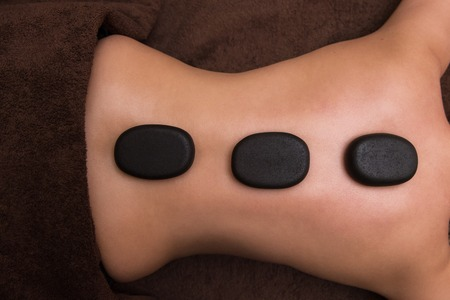 Woman receiving a therapy with hot stones in spa center, closeup photo Stock Photo