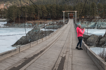Happy woman taking photos on the bridge from river at beauty sunny spring day, in Altai mountains. Travel vacation concept.