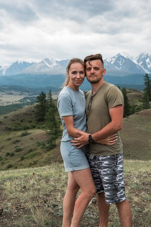 Romantic couple in the mountain, in Altai Mountains. Happy man and woman hug on the background of a mountain glacier, smiling and and look into the camera Stock Photo