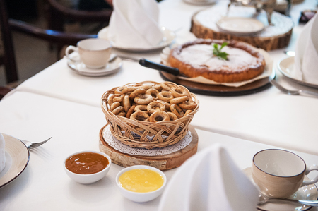 Traditional russian baked goods: pies and pretzels, samovar, honey, jam on the served table Stock Photo