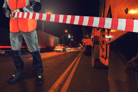 Worker blocks repair street. Concept of repairing the road in the night city