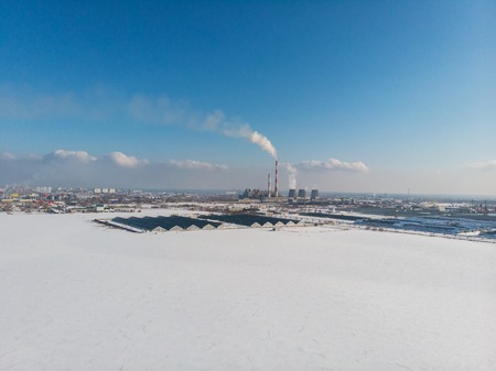 Landscape of smoking chimneys of factories in an industrial city, sunny beauty winter day. Concept of dangerous ecology in city, smoke and smog from factories and plants.