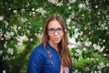 Beautiful woman portrait in the blooming garden of apple Foto de archivo - 124951859