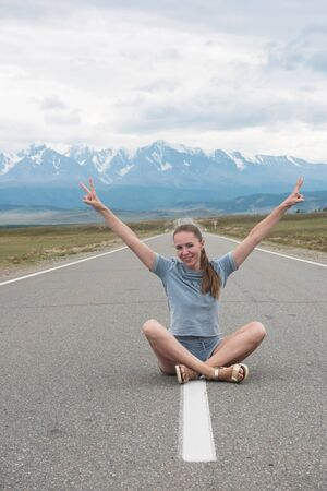 Woman sitting on the beauty road in mountain