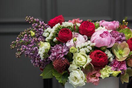 Ramo de flores de diferente belleza en caja redonda actual sobre fondo oscuro
