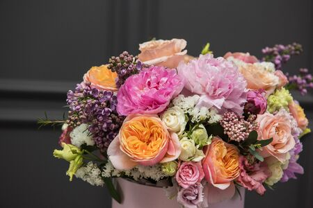 Bouquet of different beauty flowers in round present box on dark background 写真素材