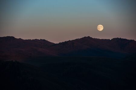 Full moon at sunset in Altai Mountains Фото со стока