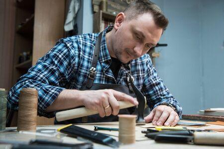 Homme travaillant avec du textile en cuir dans un atelier. Fabrication artisanale de maroquinerie.