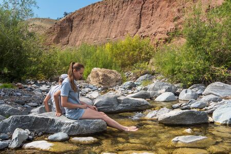 Woman with her son have rest on mountain river in Altai mountain, beauty summer landcape 写真素材