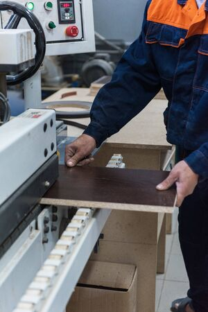 Furniture production or craft concept: worker making the wood surface of furniture part with special machine
