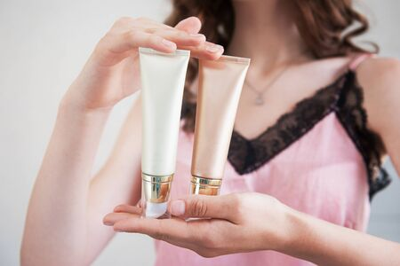 Skin care concept. Close up of female hands holding cosmetic cream tubes.