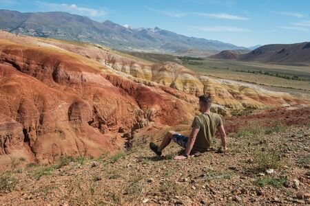 Relaxing man in Valley of Mars landscapes in the Altai Mountains, Kyzyl Chin, Siberia, Russia