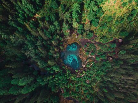 Beautiful Geyser (blue, silver) lake with thermal springs that periodically throw blue clay and silt from the ground. Aerial drone view. Aktash, Altai mountains, Russia 写真素材 - 130042022