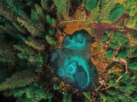 Beautiful Geyser (blue, silver) lake with thermal springs that periodically throw blue clay and silt from the ground. Aerial drone view. Aktash, Altai mountains, Russia 写真素材 - 130042025