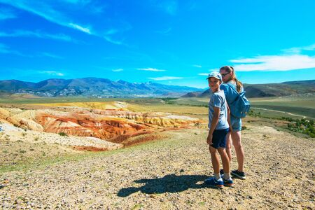 Teen boy and his mother in valley of Mars landscapes in the Altai Mountains, Kyzyl Chin, Siberia, Russia