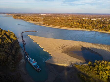 Cleaning and deepening by a dredger on the river. Ob river, Siberia, Russia