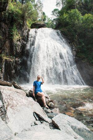 Woman at Korbu Waterfall on the Lake Teletskoye in autumn Altai Mountains.