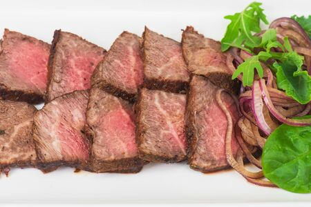 Plate with meat cutting and fresh greens on white plate Stock Photo