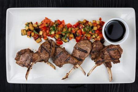 Roasted lamb ribs with vegetables on white palte