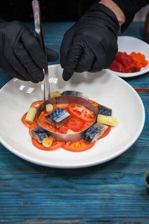 Processo di cottura del piatto di pesce escabeche con caviale: sgombro in marinata con verdure, su un piatto sullo sfondo blu di legno. Archivio Fotografico