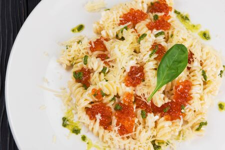 Pasta with parmesan cheese basil and red caviar. The concept of Italian cuisine.