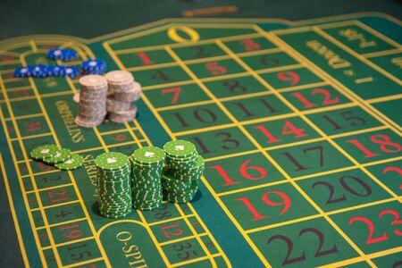 Concepto de casino, juegos de azar y entretenimiento: mesa de ruleta verde con fichas de colores listas para jugar