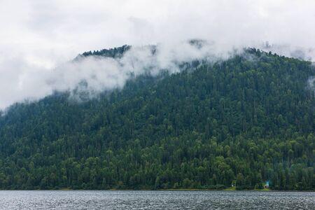 Teletskoye lake in Altai mountains, Siberia, Russia. Foggy summer morning.