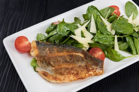 Grilled Dorado fish fillet with spinach, tomato and cheese