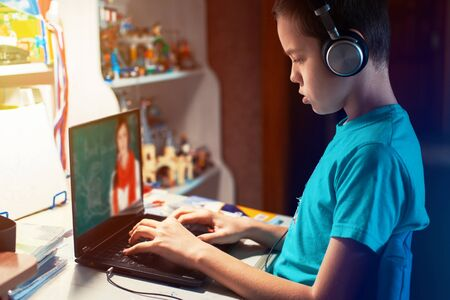 Distance learning or online education conference concept. Schoolboy studies at home and does school homework by laptop Stock fotó