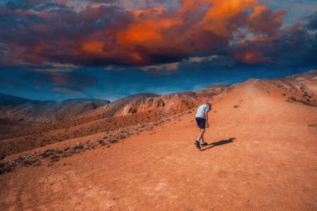 Teen boy in valley of Mars landscapes with beauty sky sunset