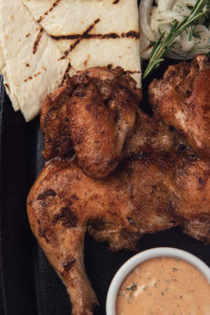 Appetizing grilled juicy chicken with golden brown crust served with barbeque sauce, rosemary and pita bread.