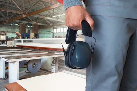 Wooden furniture production. Worker wearing protective headphones at factory