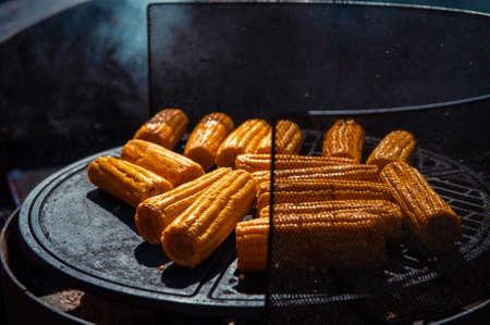 A professional cook prepares corn on the grill outdoor, food or catering concept